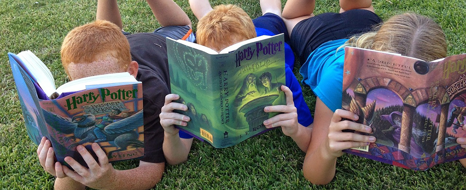 Three children reading Harry Potter books