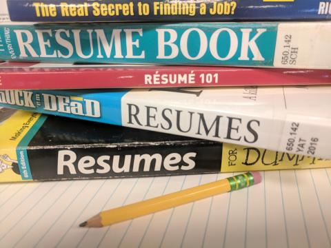 pencil paper and stack of resume books