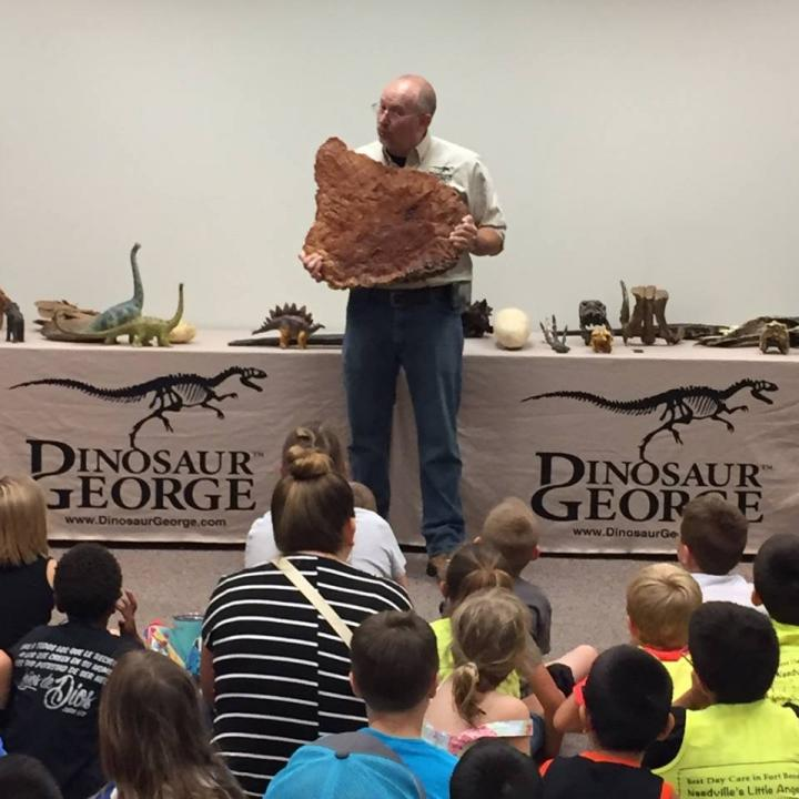 Man holding huge fossil in front of an audience of children
