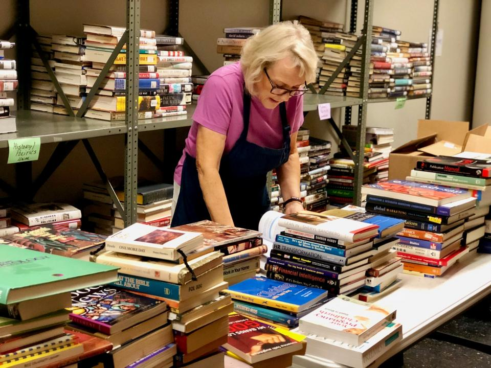 Friends member working at a book sale for the George Memorial branch